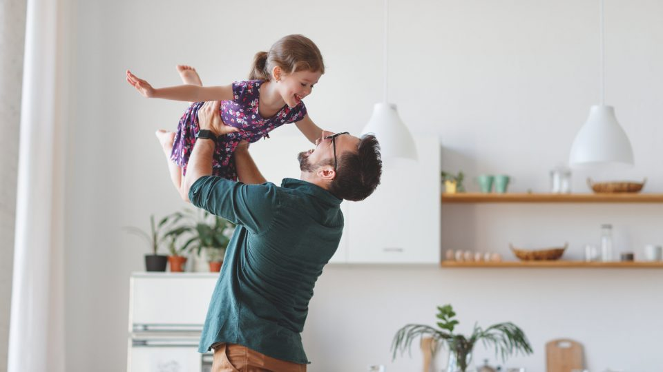 Father holding child happily in the air